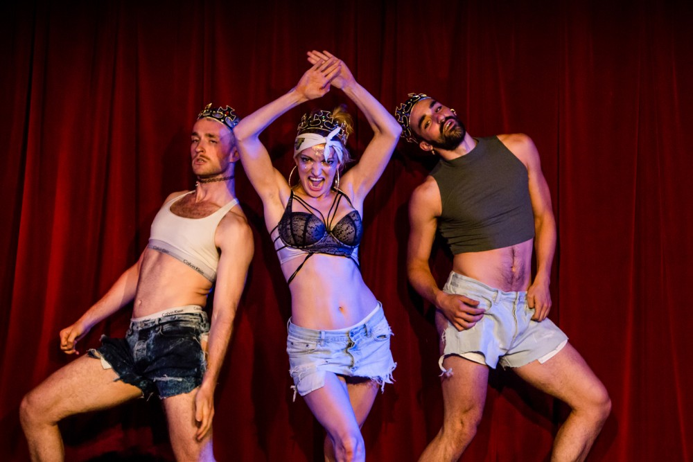 A woman dressed in underwear has her hands up in aggression, she has a man on each side. They are all wearing plastic crowns.