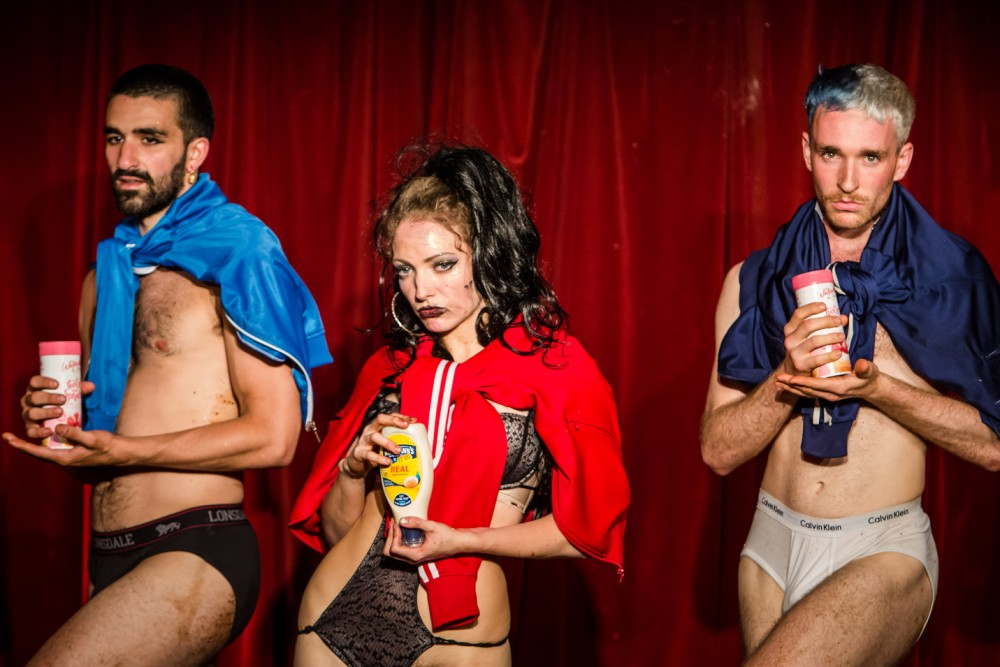 A woman dressed in underwear with a man on each side stand in front of a red curtain. They are holding containers of food in their hands.