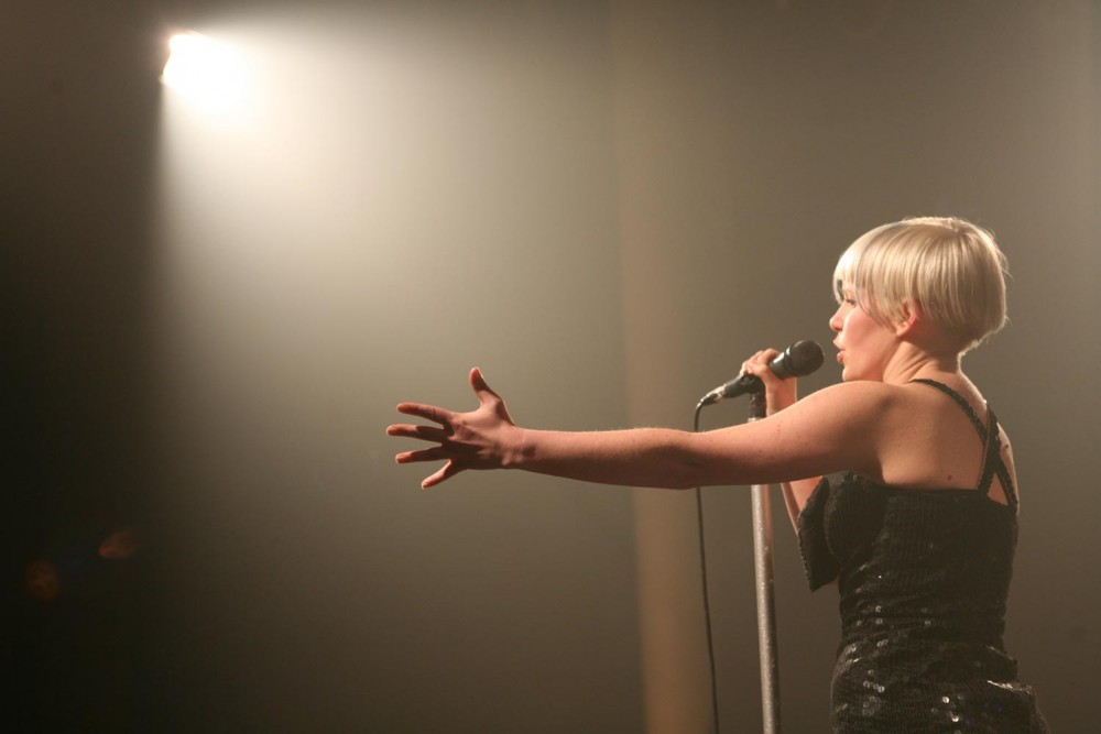 A woman stands in front of microphone, singing out to the audience.