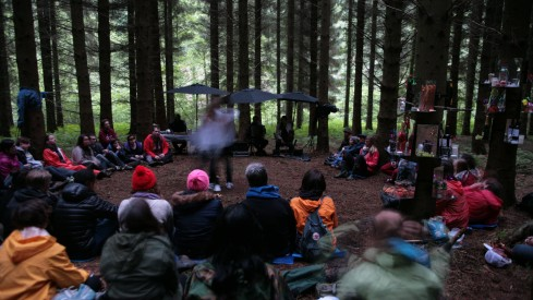 A crowd of people sit in a woodland. A few are holding umbrellas, someone in performing in the centre of the space.