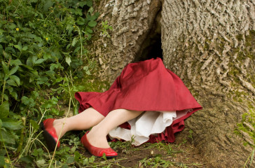 A woman dressed is sticking out of the bottom of a tree, she is wearing a red dress and red shoes.