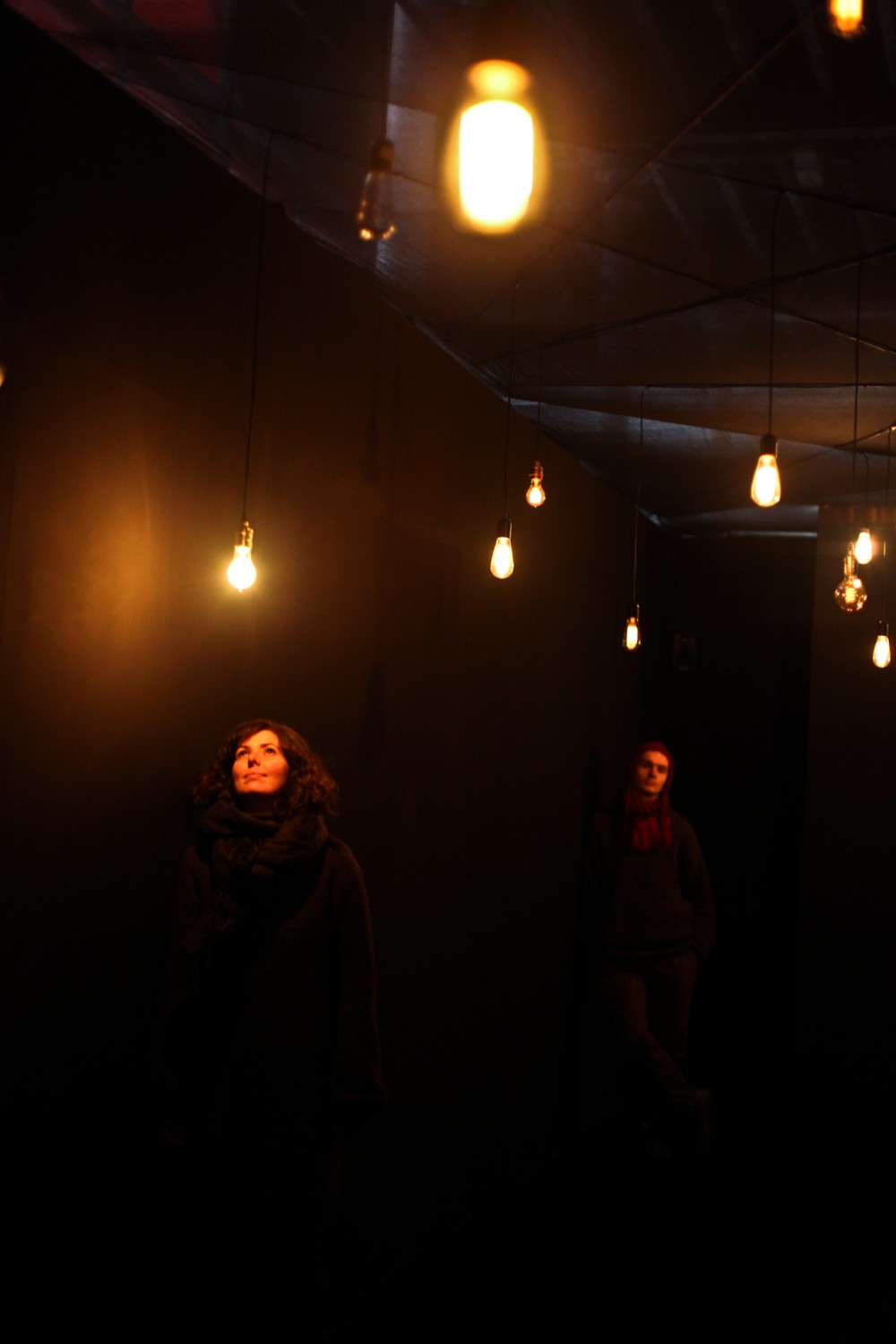 A woman stands in a black room with different shaped light bulbs hanging from the ceiling.
