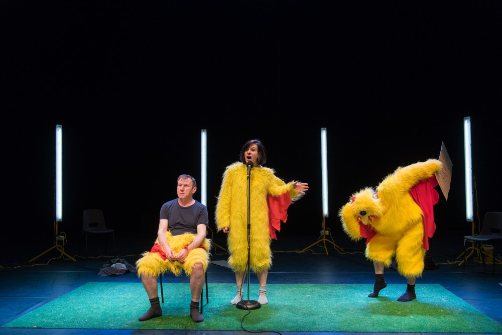 Two men and a woman are dressed in chicken suits. The woman stands in front of a microphone, one man is bent over the other man is sat down.
