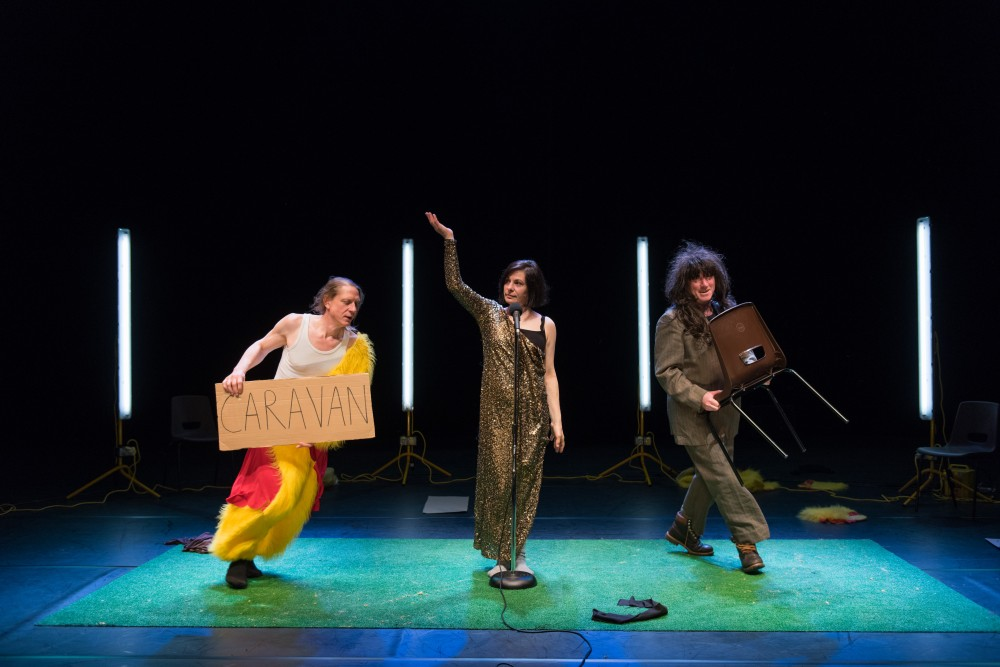 Two men and a woman are stood on stage, one man is wearing a chicken suit, the woman is wearing a dress in front of a microphone and the other man is wearing a black wig and is holding a chair.