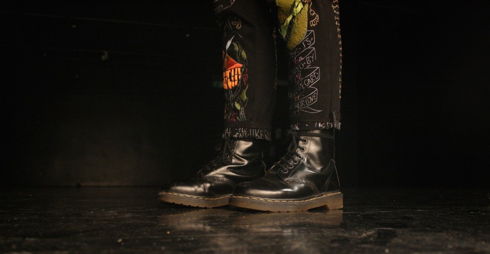 Two legs wearing colourful patterned trousers and back boots stand alone in the centre of the image.