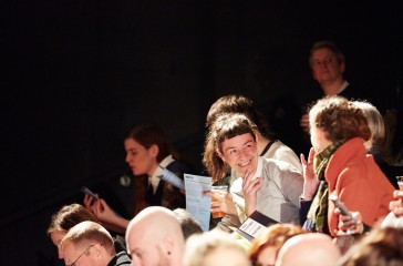 An audience clip, a woman is sat with her friend laughing.