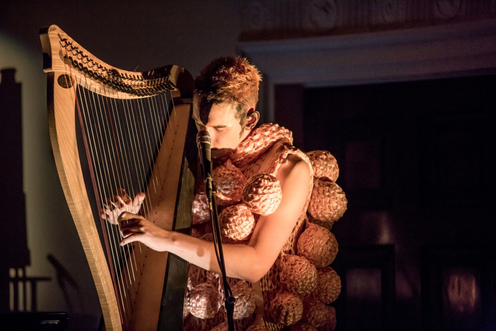 A man wearing a knitted outfit, sits playing the harp.