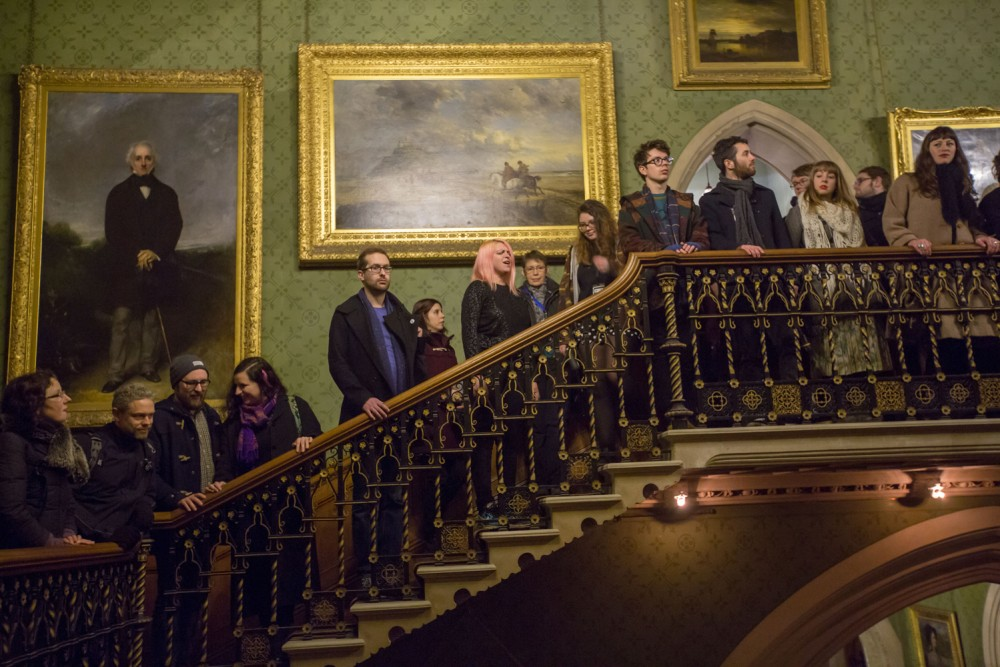 Inside Tyntesfield Manor, the audience are lined up a grand staircase. There are oil paintings on the wall behind them.