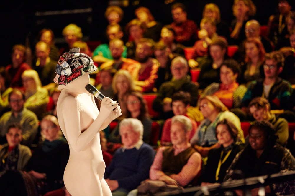A woman in a white morph suit stands with a microphone, talking to an audience.
