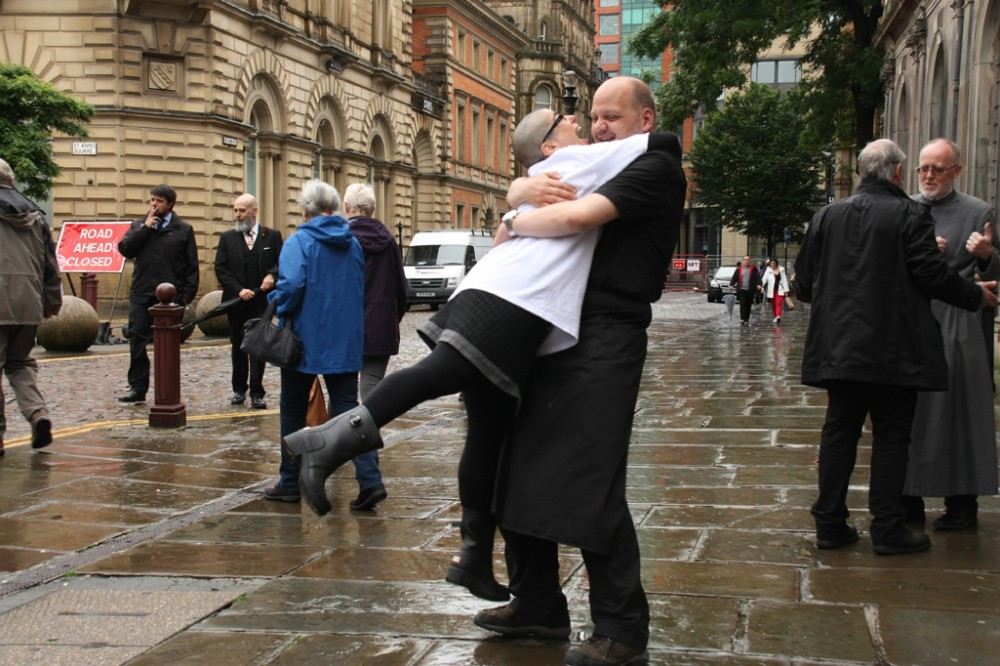 Outside a cathedral, a man lifts a woman up in joy.
