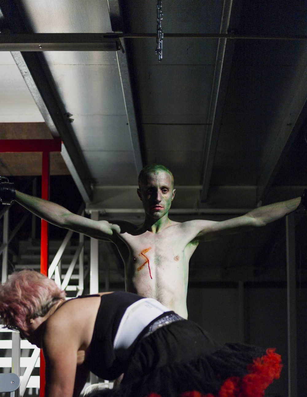 A man stands with green paint on his head and his arms stretched out. In front of him their is woman wearing a tutu, she is bent over.