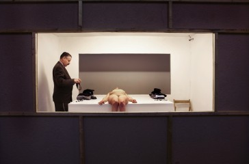 Through a gap in the wall, you see a white room. A naked woman is laid out on a white block, a man in a suit is stood looking over her.