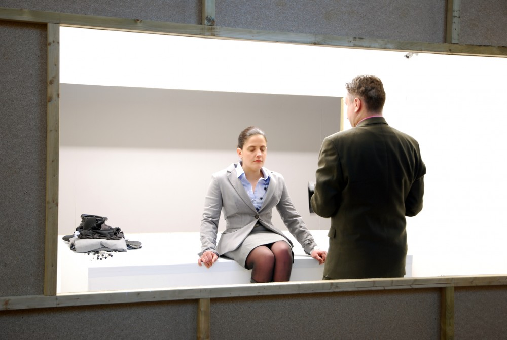 The camera is staring through a gap in the wall. A man is standing in front of a woman, the woman is sat on a white block with her eyes closed.