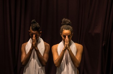 Two women, stand together in front of a red curtain. They have white material wrapped around their necks and they are holding their hands to their faces.