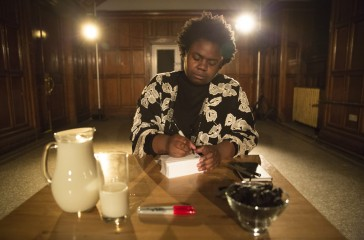 A woman sits at a table, writing something. A jug of milk is also on the table.
