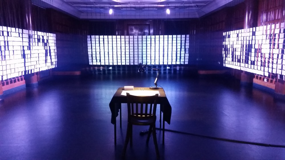 A table and chair are centred in a empty blue room.