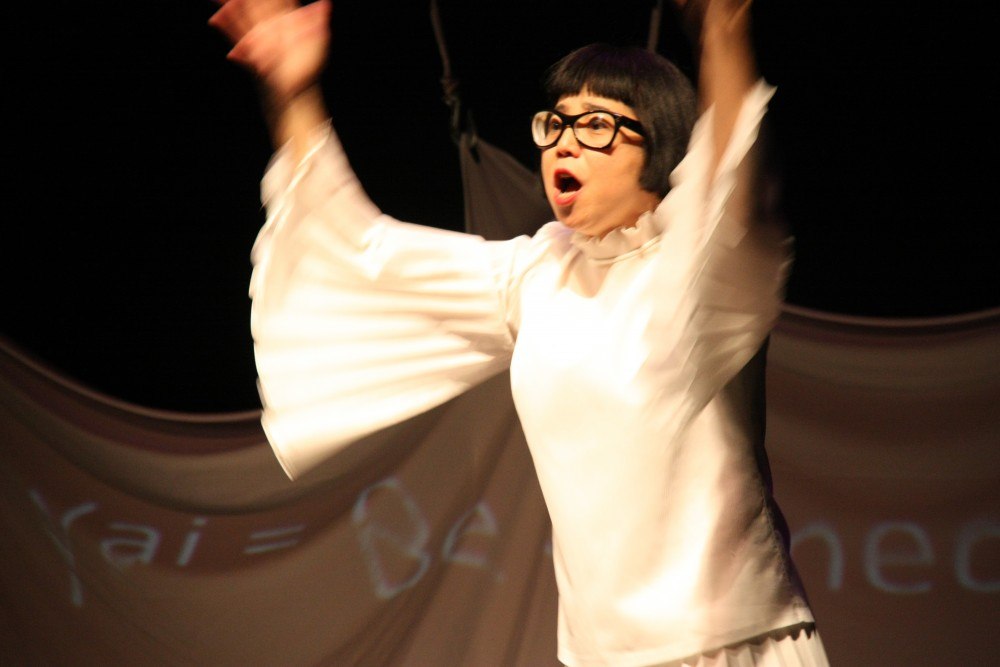 A woman dressed in white, flings her hands into the air towards the audience.