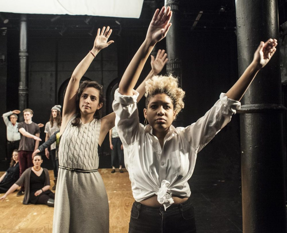 Two women stand facing the camera holding their hands up.