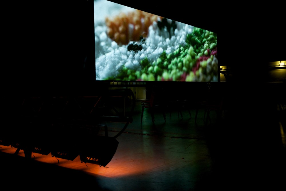 A big screen plays, there is an image of a close up of piece of material.