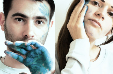 A man and a woman with blue paint on their hands, smudge the paint against their faces.
