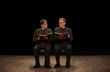 Two men both dressed in grey suits, with red jumpers sit on chairs facing the audience, they are looking directly at each other and they are both holding a brown book.