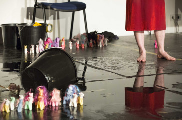 A woman in a red dress stands on a wet floor, she is surrounded by empty buckets and collections of My Little Pony figures.