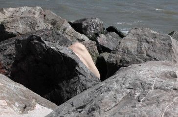 A naked women is hiding among some rocks on a beach.