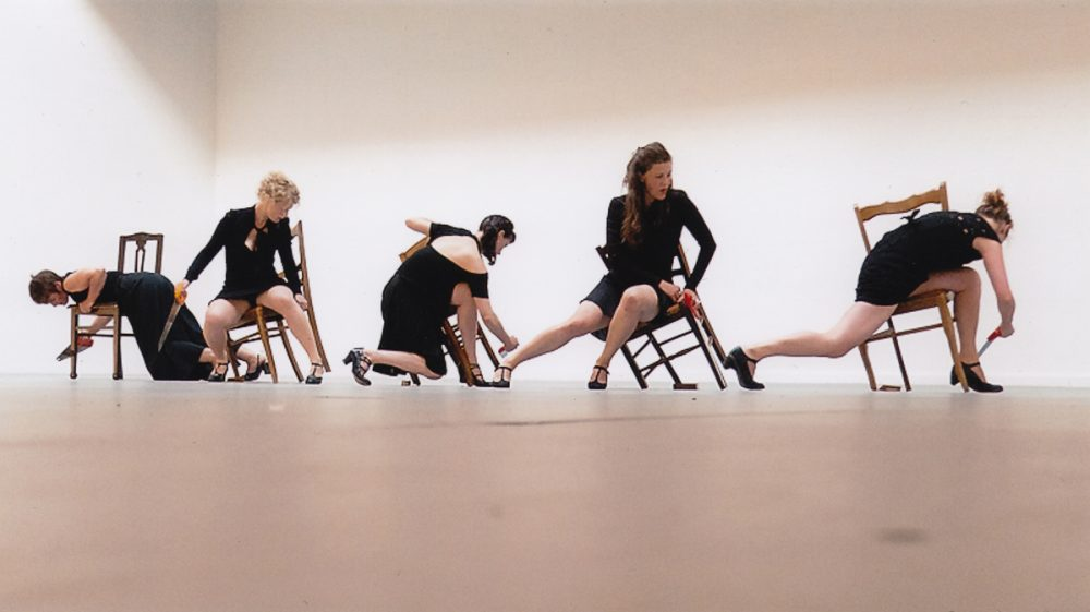 Five women dressed in black dresses, hang and balance off broken chairs.
