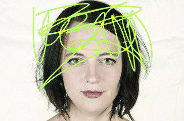 A woman with short brown hair faces the camera, there is green graffiti based across the image.