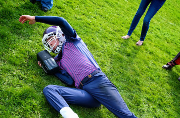 A man lying on the grass dressed in an American Football costume holding a ball, surrounded by a circle of audience members