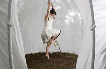 A female dressed in white dances inside a white tent, the floor is covered in soil.