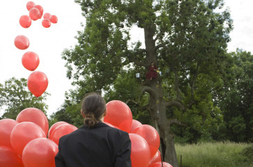 A female in a red dress sits in a tree. At the bottom of the tree a figure stands holding a bunch of red balloons.