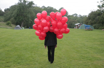 Figure is walking on grass, their face is hidden behind red balloons.