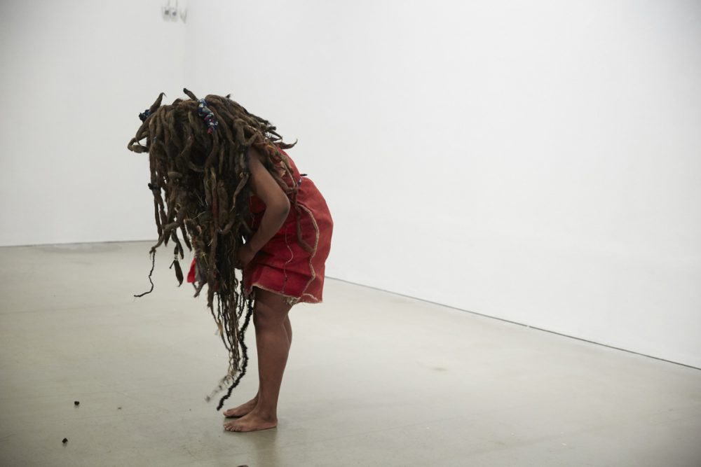 A figure is dressed in red and has long hair and dreadlocks wrapped aorund their face and head.