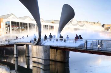 People walk across a bridge covered in fog.