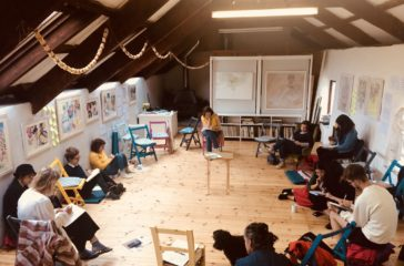Ten people sit in a circle on a mix of chairs and cushions. They all have notebooks and are writing in them