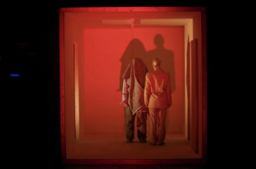 Two figures stand in a wooden box which is lit up with red light, their shadows are cast ont he wall and we can't see their faces