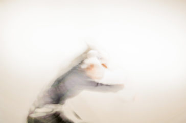 Out of focus image of a person dancing with their arms above them