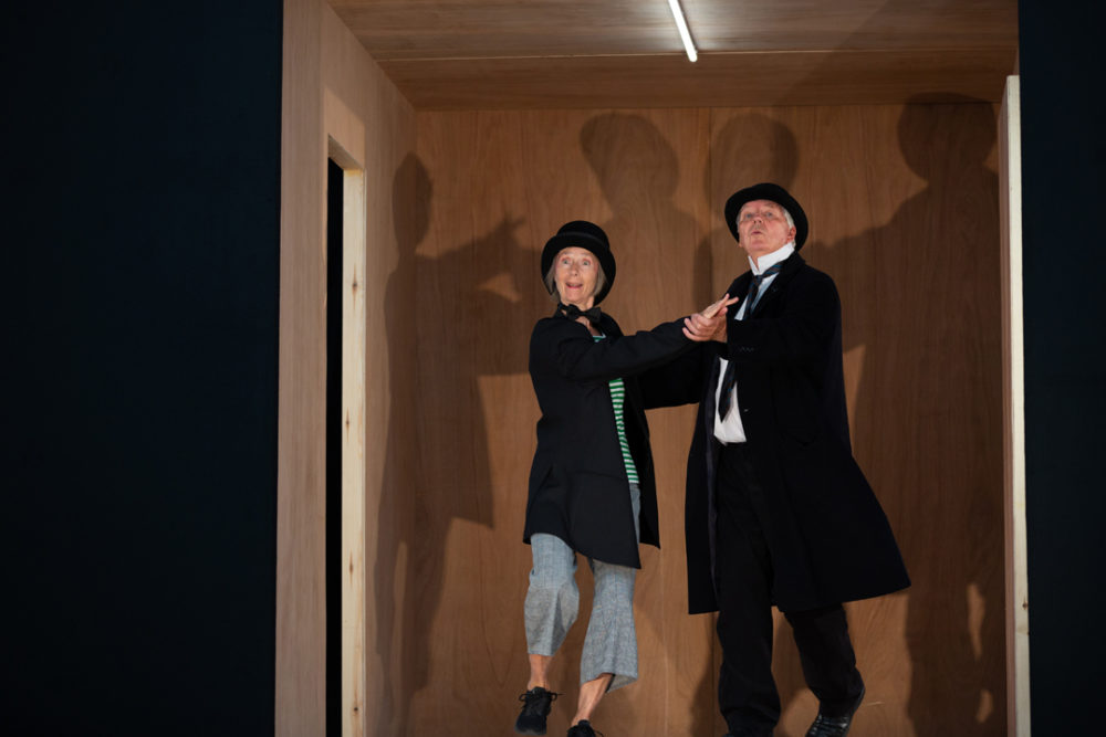 A man and a woman dressed in bowler hats and smart black jackets dancing.