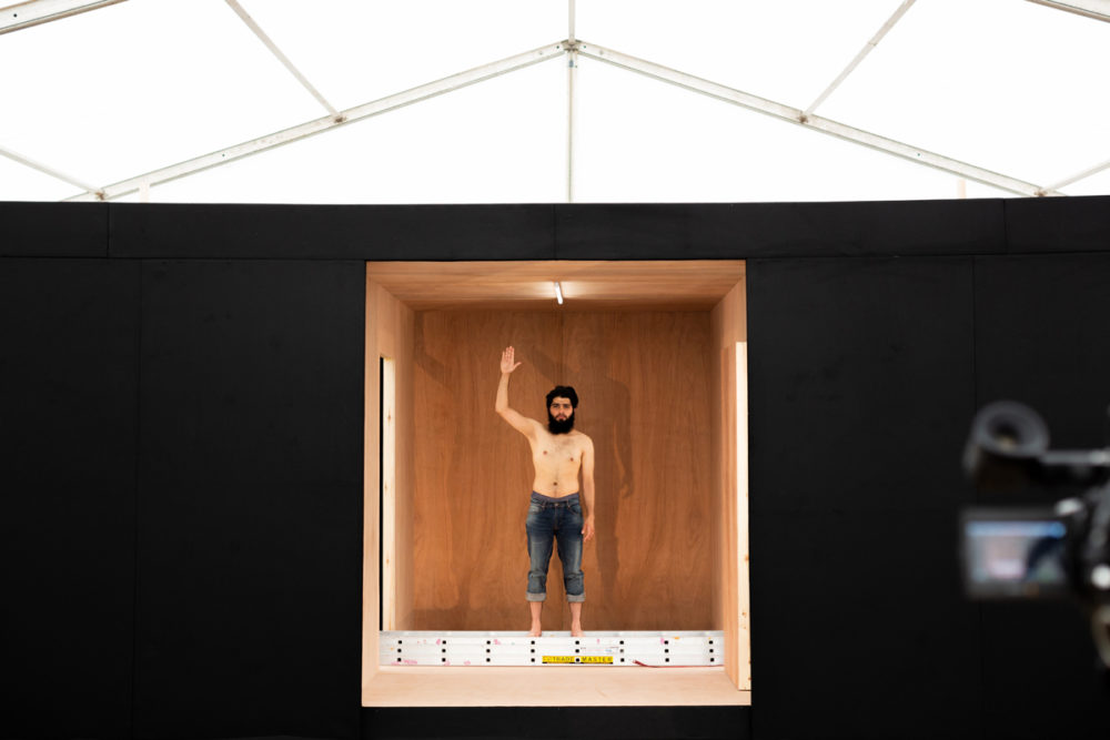 Topless man waves from small room