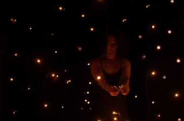Person stands in a dark room full of tiny yellow lights