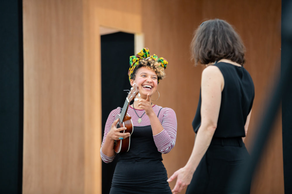 A woman with holds a ukulele and laughs