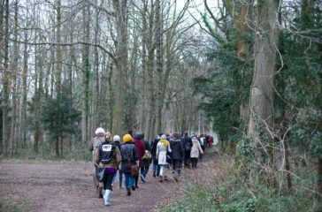 A group of people walk though a woods in winter