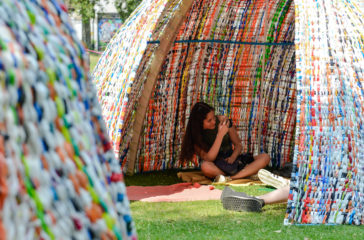 A girl sits in a dome made of plastic bags