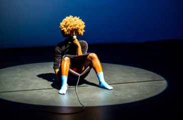 Artist Ishimwa Niyizi sits in a spotlight on a stage