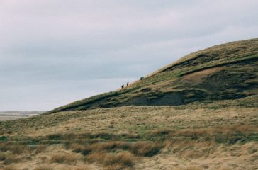 Three small figures walk up a hill