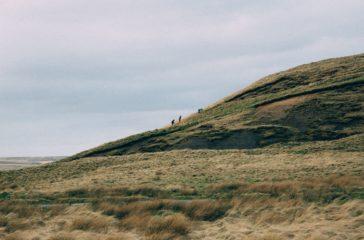 Three small figures walk up a hill