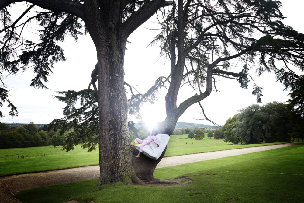 Chisara Agor, Creative Exchange Lab artist in a tree lying on a mattress