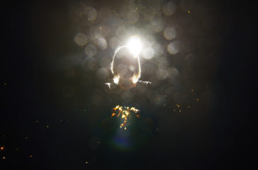 A woman stands in a dark space holding up a collection of lights to the camera