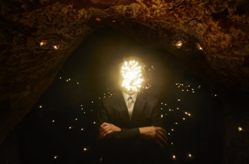A man with a face made of lights stands in a cave which contains lots of tiny lights